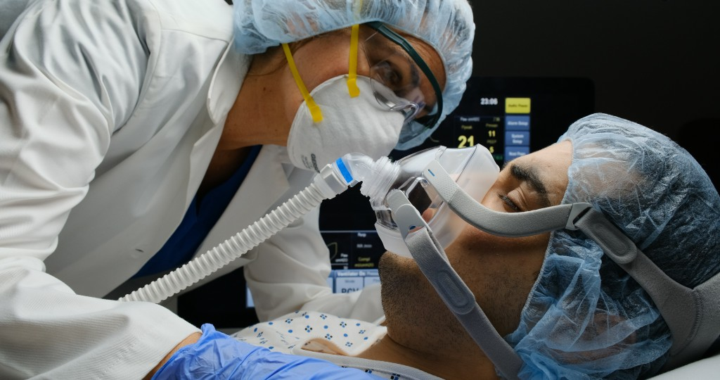 Female Doctor Checking On Covid 19 Infected Patient While Connected To A Ventilator