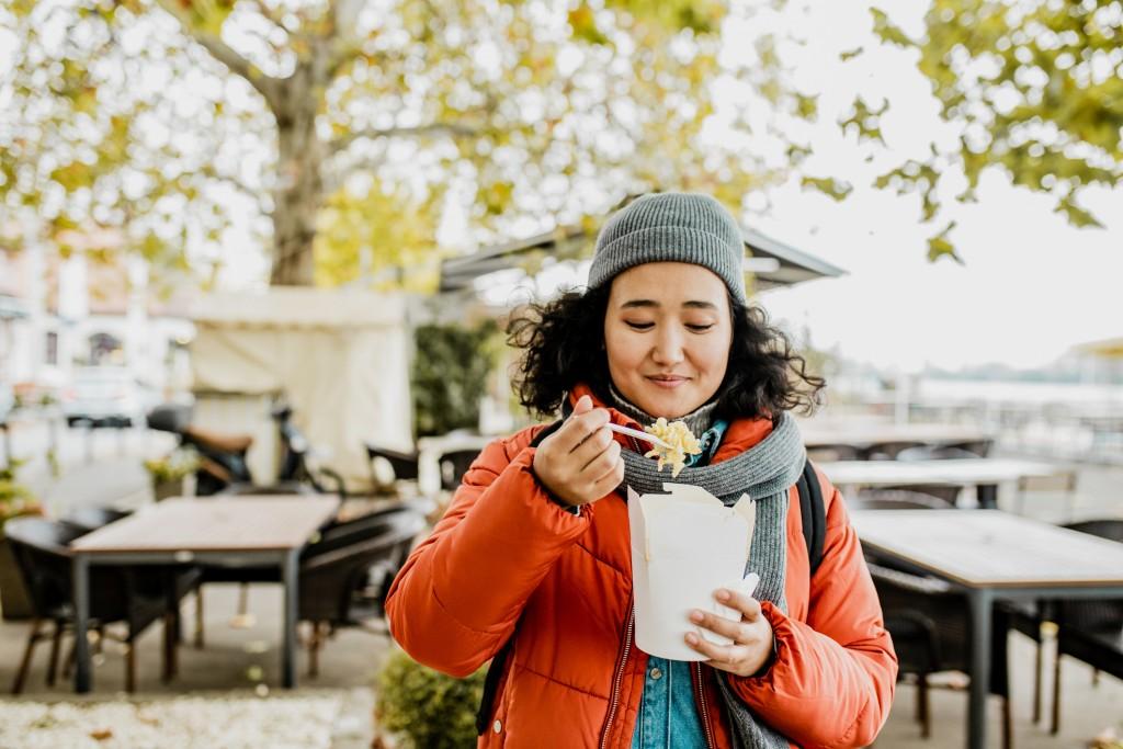 Asian Woman Eating Pasta Outdoors